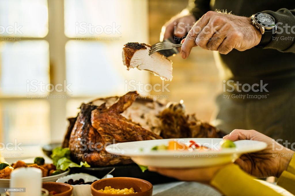 Unrecognizable man putting a piece of turkey meat on a plate during...