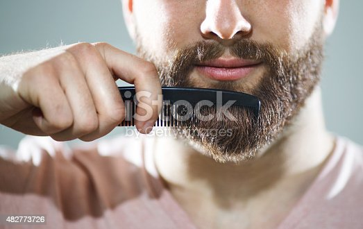 Closeup of unrecognizable caucasian man combing his beard and mustach with small black comb.He has neat,fully grown brown beard and mustache.Studio shot over gray background. ,=Front view.