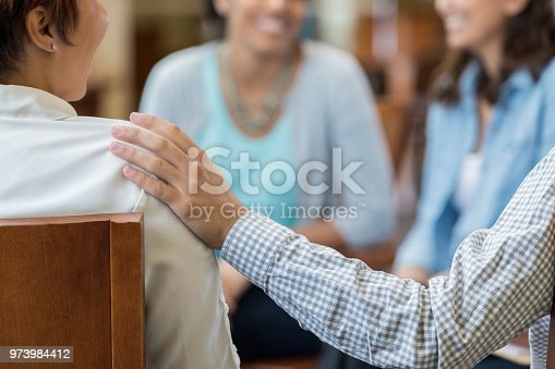 956725746 istock photo Unrecognizable man comforts woman in therapy session 973984412