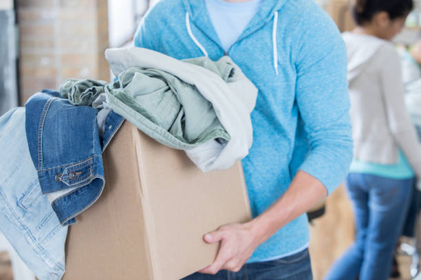 Unrecognizable man donates clothing to shelter stock photo