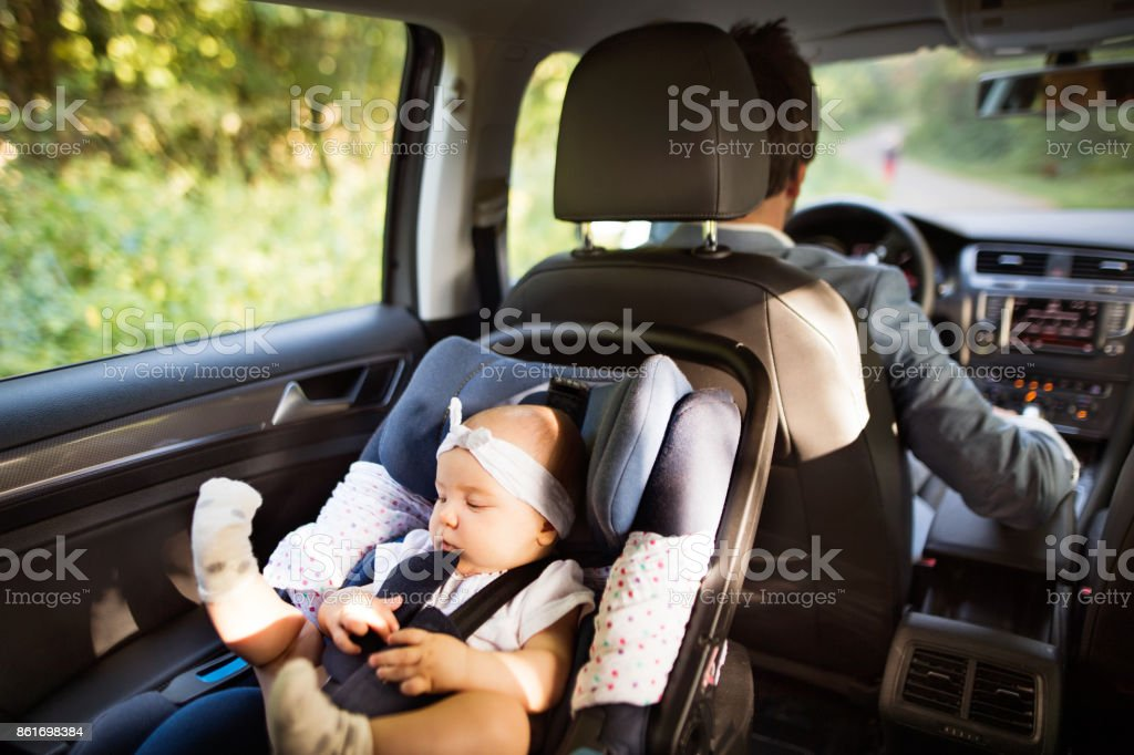 Unrecognizable man driving with a baby girl. stock photo