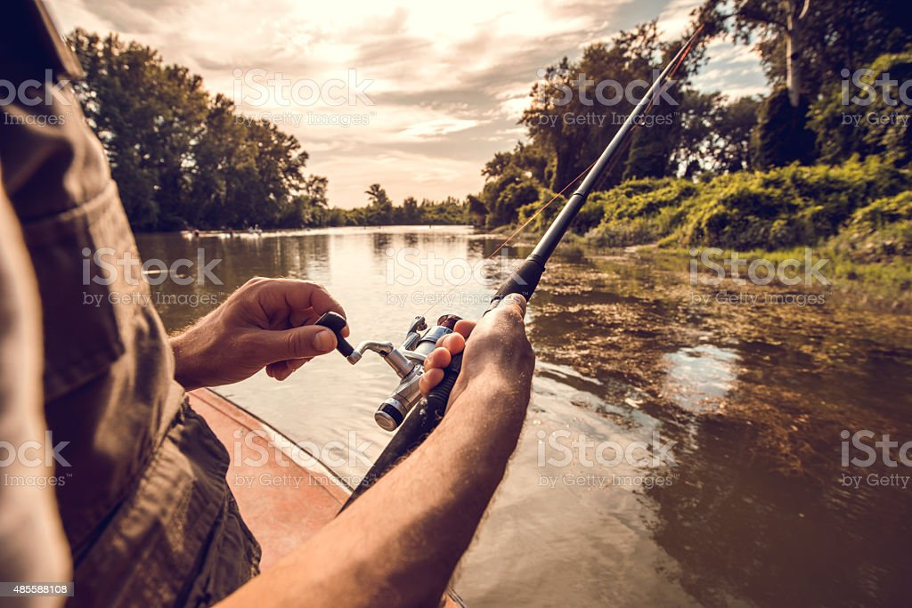 Unrecognizable man fly-fishing on the river. stock photo