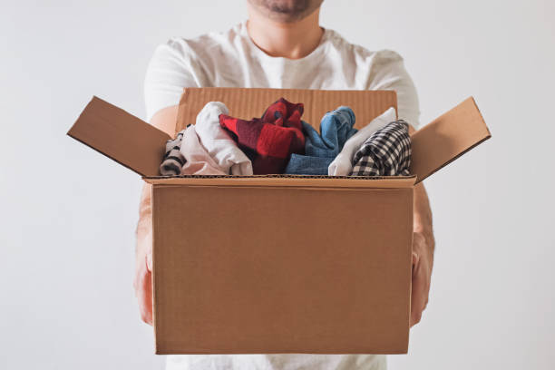 Unrecognizable man holding a cardboard box full of clothes close-up. stock photo