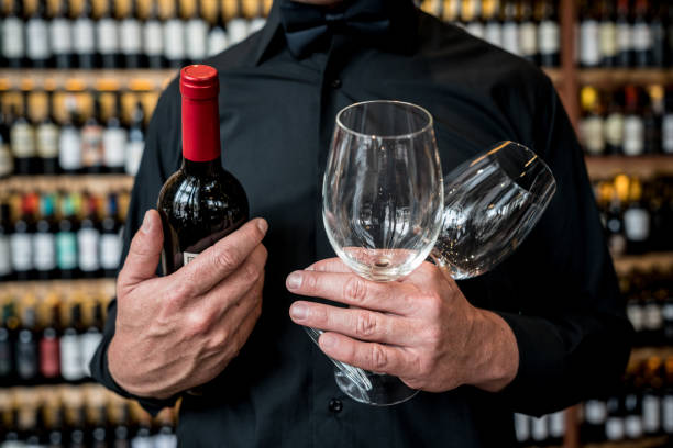 Unrecognizable man holding glasswines and a wine bottle at a restaurant stock photo