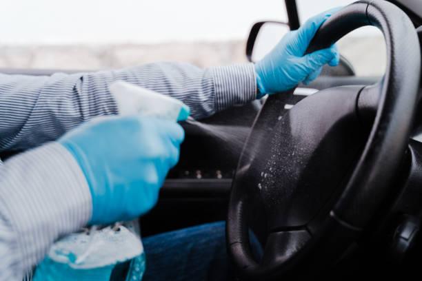 hombre irreconocible en un coche usando gel de alcohol para desinfectar el volante durante el coronavirus pandémico cóvido-19 - foto de stock