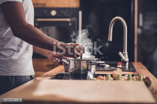 Unrecognizable man stirring soup in a saucepan while making lunch in the kitchen.