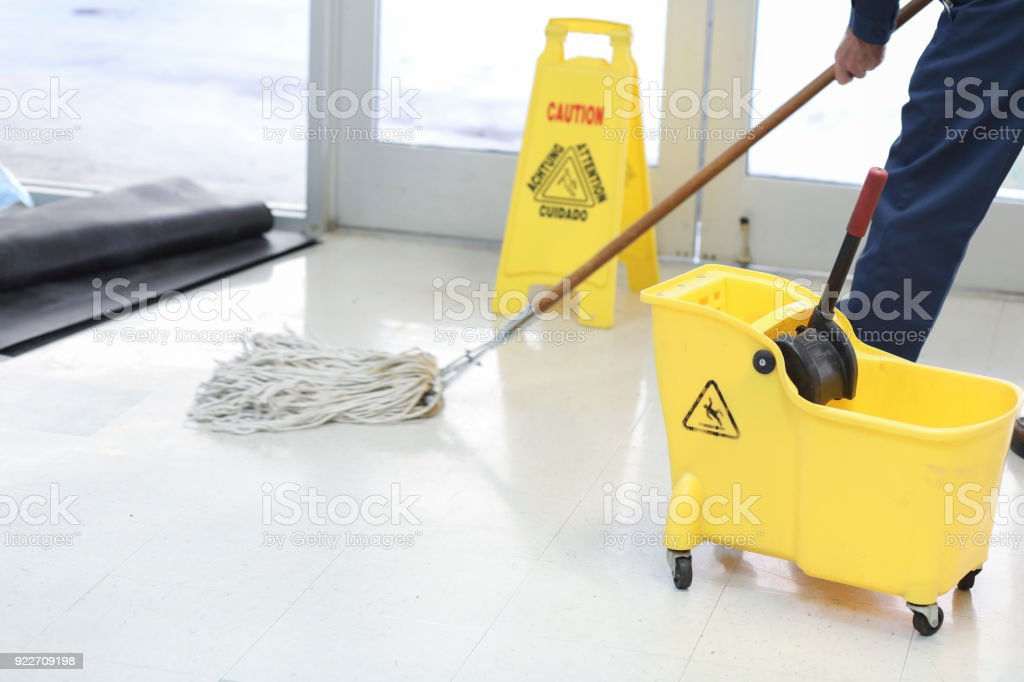 Unrecognizable man mopping floor in office building. stock photo
