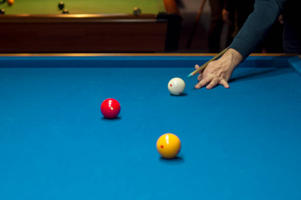 unrecognizable man playing billiard taking aim - pool cue stock photos and pictures