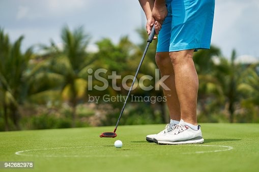 unrecognizable man putting in golf course in summer