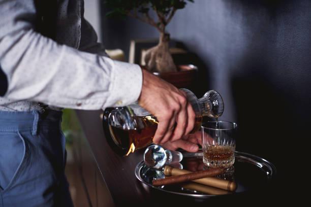 위스키 한 잔을 따르고 인식할 수 없는 남자 - 스카치 위스키 뉴스 사진 이미지