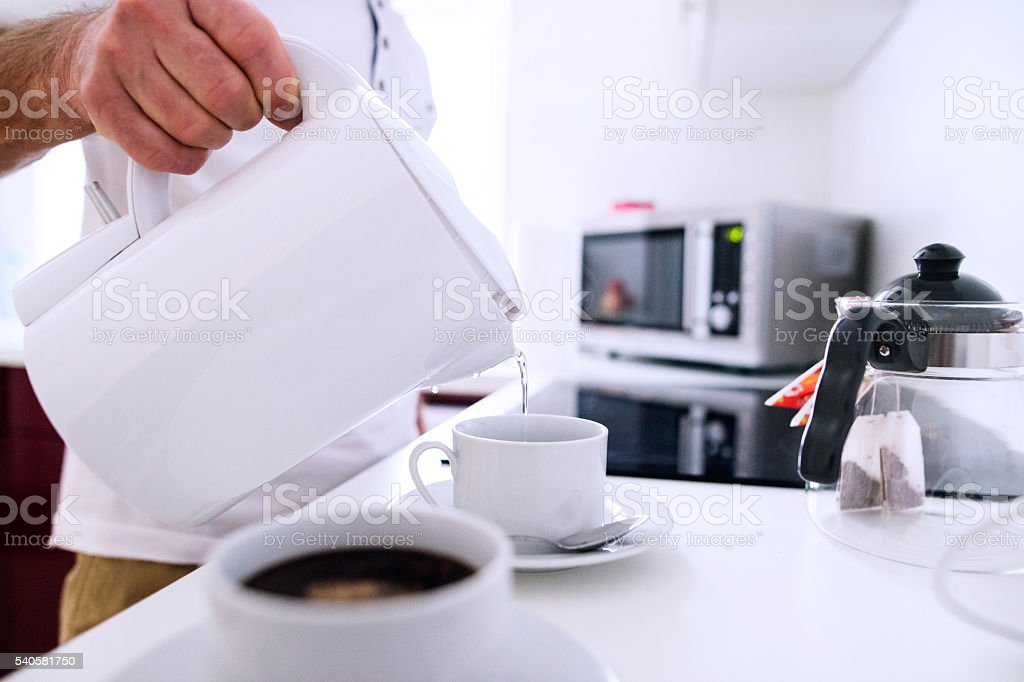 Unrecognizable man preparing coffee. Pouring water into a cup. stock photo