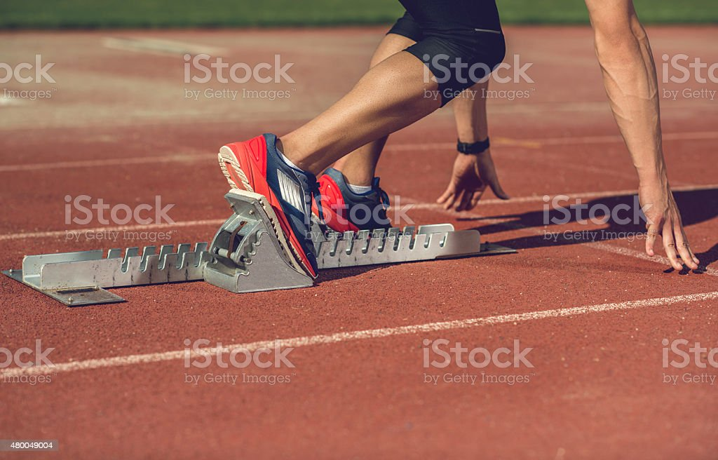 Unrecognizable man preparing to start a race on running track. stock photo