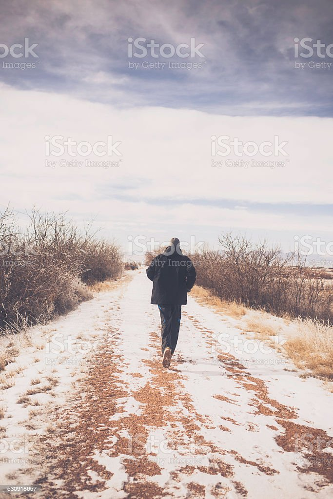 Unrecognizable man running in snow storm stock photo