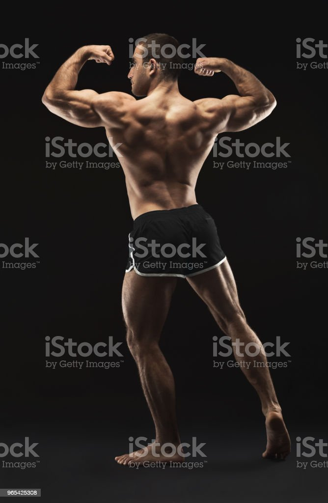 Unrecognizable man shows strong back muscles closeup zbiór zdjęć royalty-free