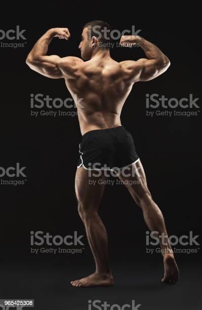 Foto de Irreconhecível Homem Mostra Fortes Músculos Das Costas Closeup e mais fotos de stock de Academia de ginástica