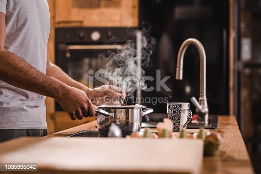 Unrecognizable black man making lunch in the kitchen and stirring soup.
