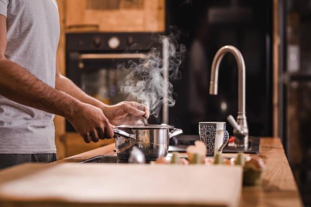 onherkenbaar man soep in een pan roeren terwijl het maken van de lunch in de keuken. - steelpan pan stockfoto's en -beelden