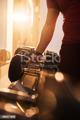 Unrecognizable person taking dumbbells in a gym.
