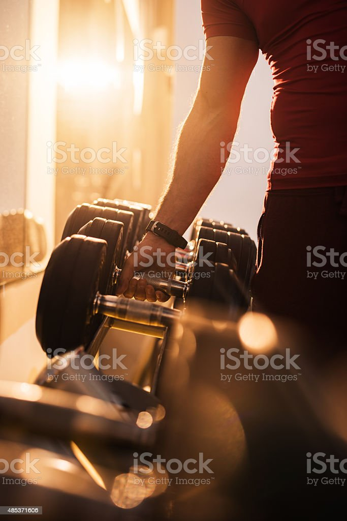Unrecognizable man taking dumbbell from a rack at gym. stock photo