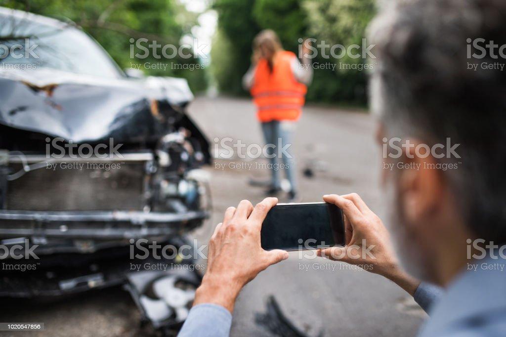 Nicht erkennbare Mann ein kaputtes Auto nach einem Unfall zu fotografieren. – Foto