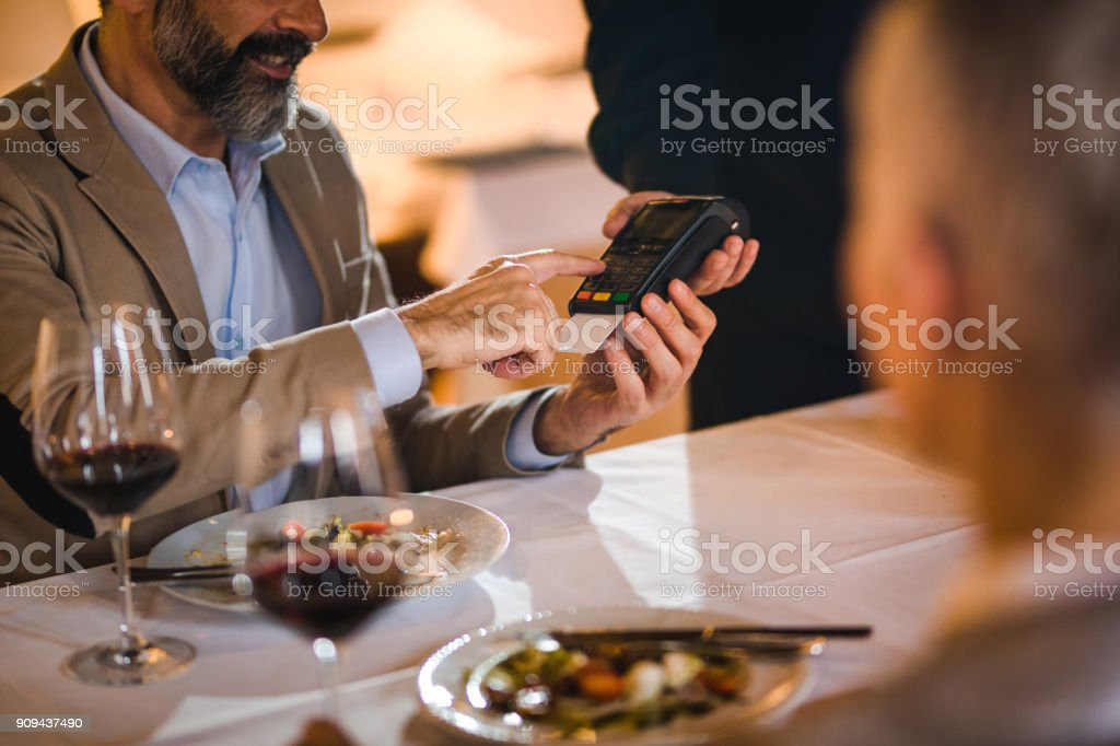 Unrecognizable mature man paying restaurant bill with credit card.