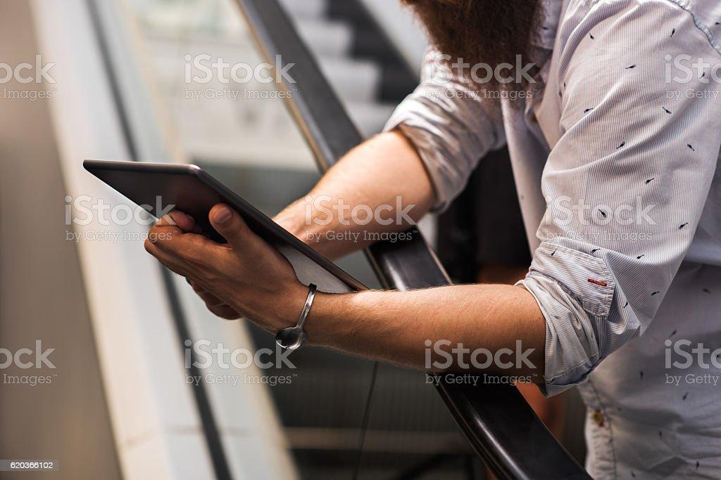 Unrecognizable man using digital tablet on escalator. zbiór zdjęć royalty-free