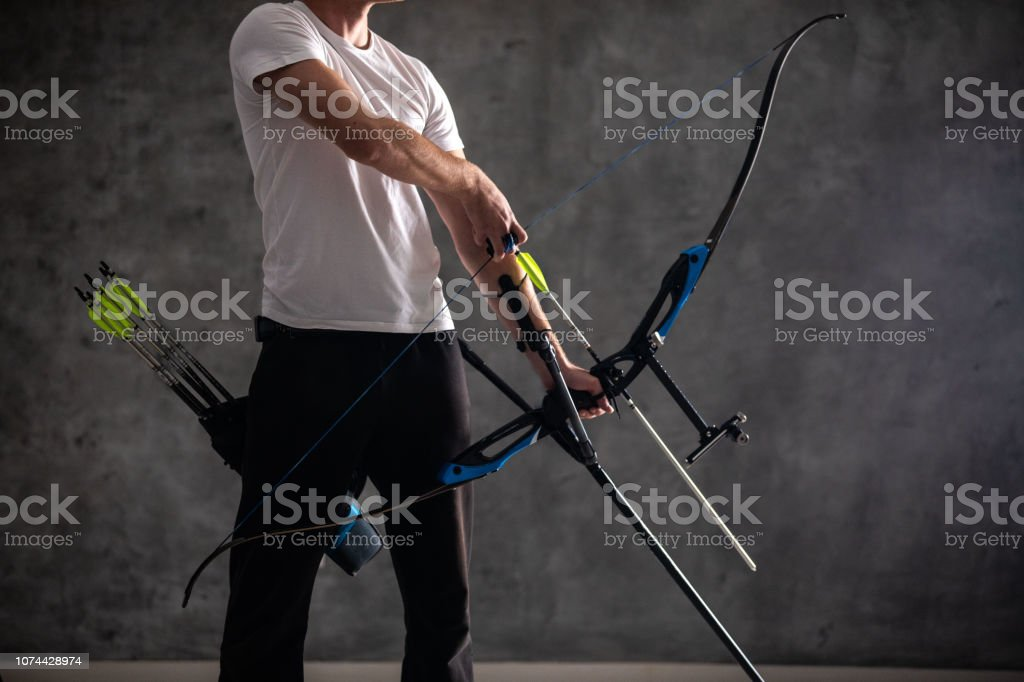 Unrecognizable man holding bow and arrow indoor
