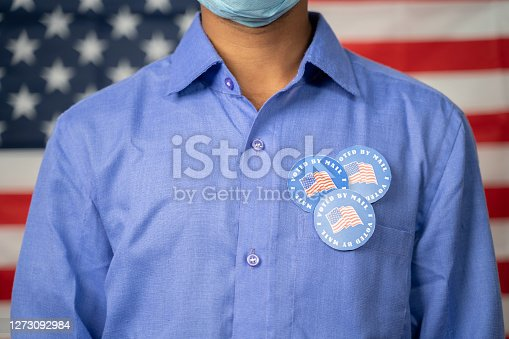 Unrecognizable Man with multiple I voted by mail sticker on shirt with US flag as background - Concept of fraud in US election mail-in voting or vote by mail.