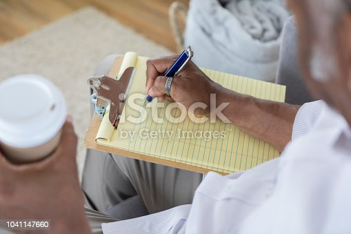 High angle view of unrecognizable African American man writing on a yellow note pad. He is also holding a coffee cup.