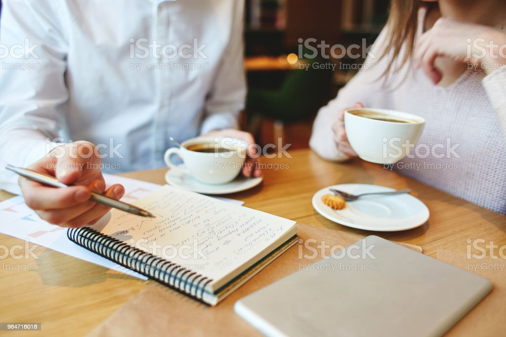Unrecognizable management students having coffee in cafe and discussing notes in notepad royalty-free stock photo
