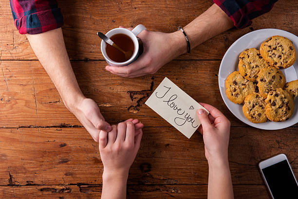 unrecognizable mans and womans hands. romantic message. tea and - i love you stock photos and pictures