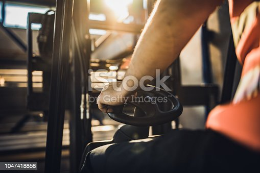 Close up of unrecognizable manual worker driving a forklift in a factory.