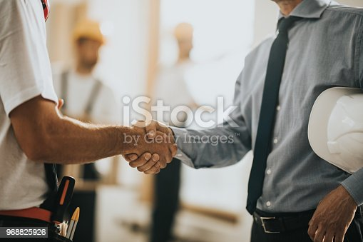 istock Unrecognizable manual worker shaking hands with an architect at construction site. 968825926