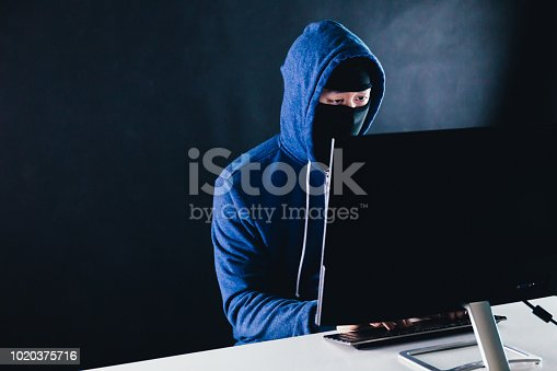812847840 istock photo Unrecognizable masked man under hoodie using a computer - data thief and online activity hacking. 1020375716