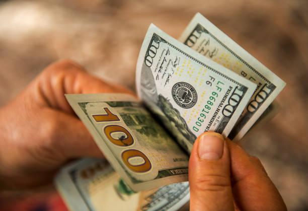 Unrecognizable mature man counting USA Dollar bills