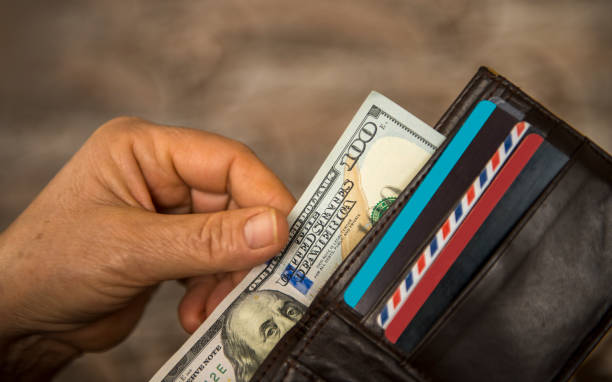 Unrecognizable mature man putting USA Dollar bill into wallet stock photo