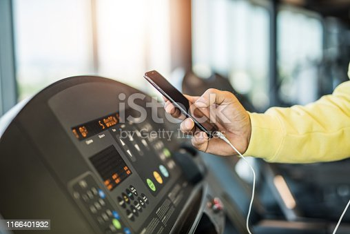 istock Unrecognizable mature man using a phone in the gym close up. 1166401932