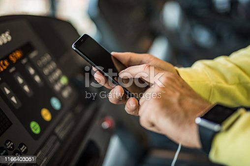 istock Unrecognizable mature man using a phone in the gym close up. 1166403051