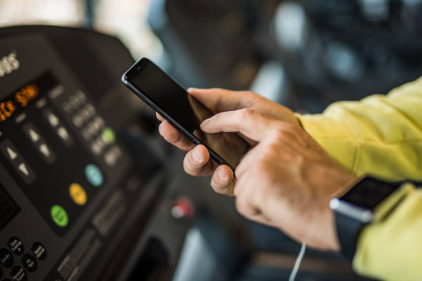 unrecognizable mature man using a phone in the gym close up. - runner rehab gym foto e immagini stock