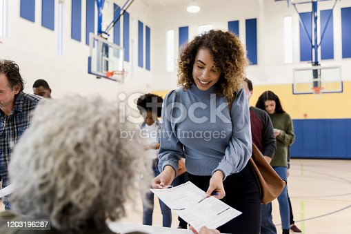 The unrecognizable mature adult female polling place volunteer assists the mid adult woman with the document she needs to be aloe to vote.  Other voters use smart phones while waiting in line.