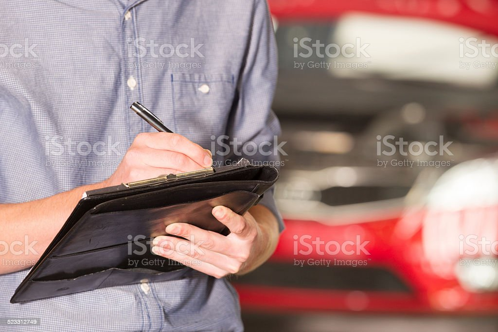 Unrecognizable mechanic in front of car stock photo