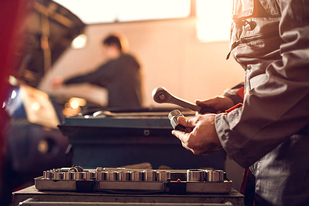 Unrecognizable mechanic with a socket wrench in a repair shop. Unrecognizable repairman holding a socket wrench and bolt in a repair shop. socket wrench stock pictures, royalty-free photos & images