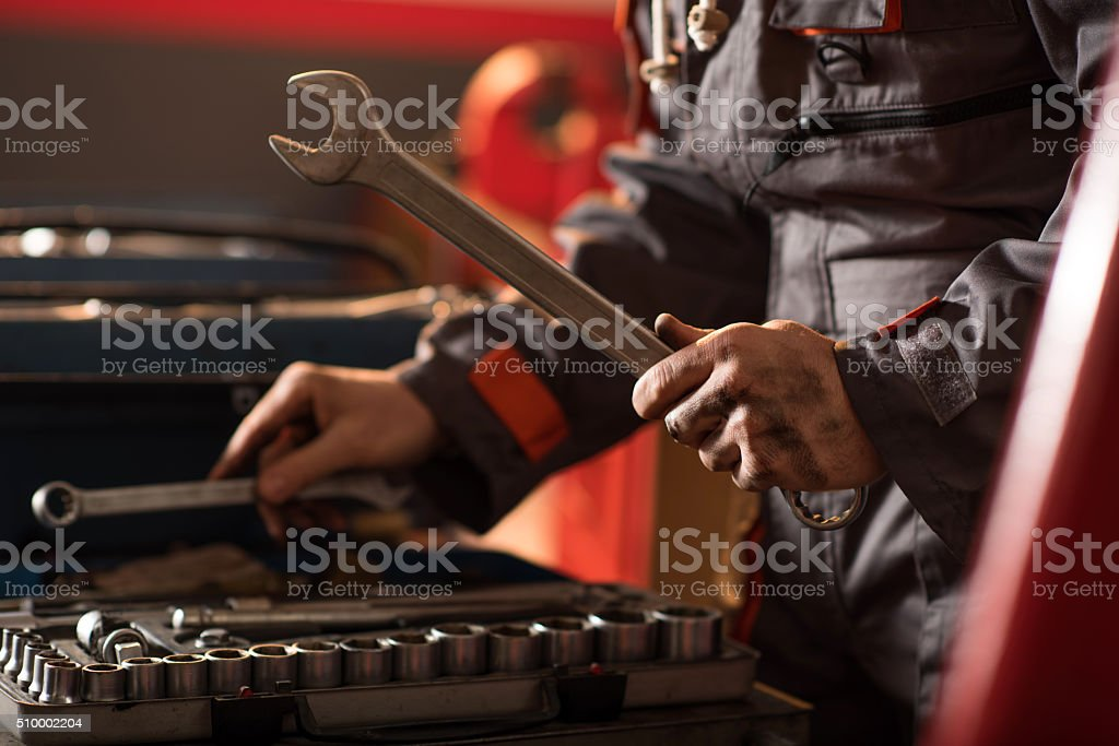 Unrecognizable mechanic with a wrench in a repair shop. stock photo