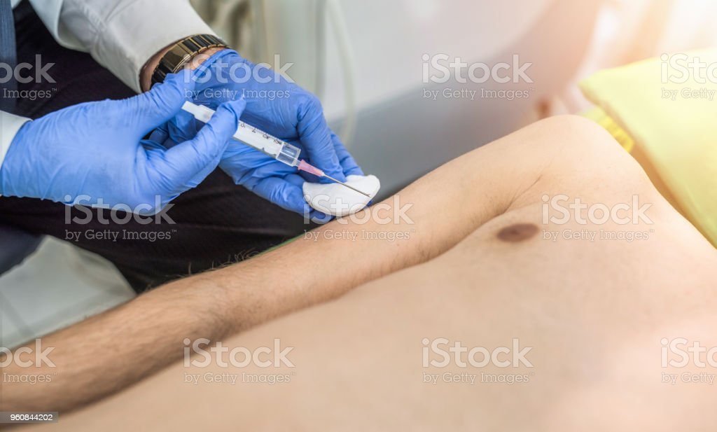 Unrecognizable mid adult man taking a vaccine. stock photo