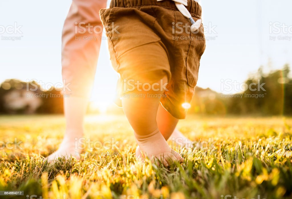 Unrecognizable mother and baby walking outside. stock photo