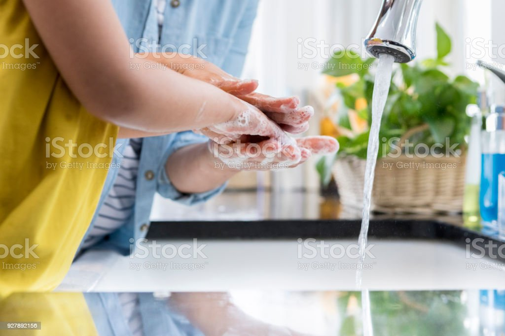 Unrecognizable mother helps child wash hands stock photo