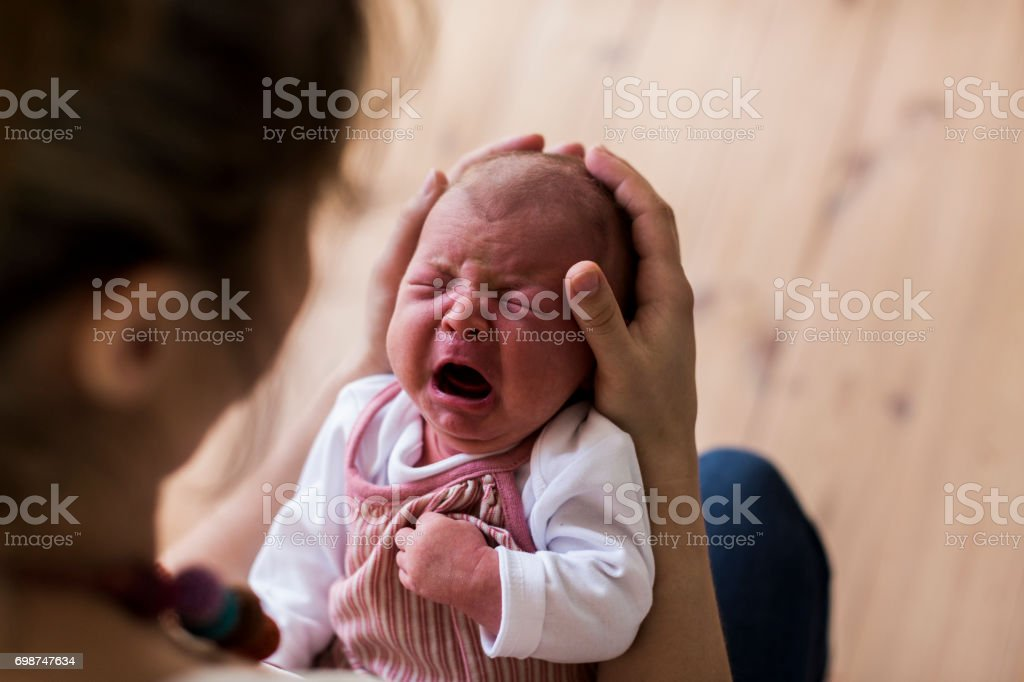 Unrecognizable mother holding crying newborn baby girl. stock photo