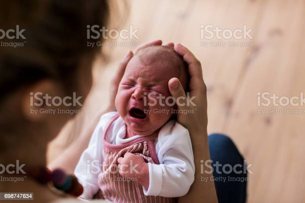 Unrecognizable young mother at home holding her crying newborn baby girl.