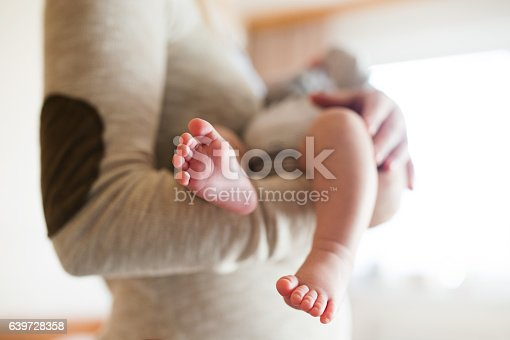 Unrecognizable mother holding her newborn baby son in her arms, close up of legs and hands.