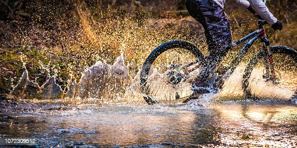 Unrecognizable mountain biker splashing and spraying water as he cycles over a stream of water in a forest.